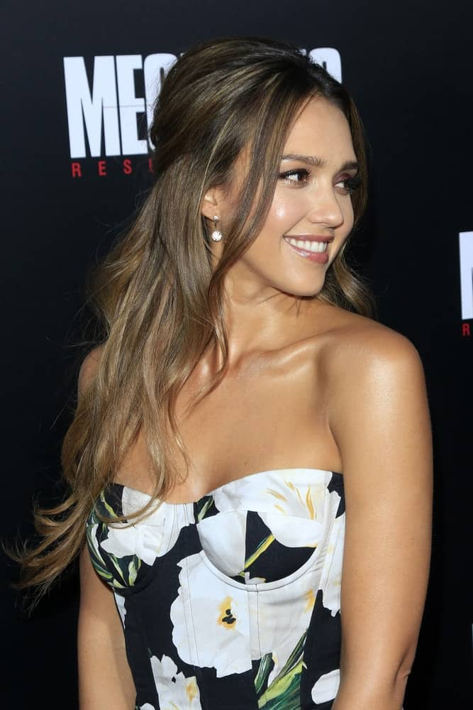"Jessica Alba attended the ""Mechanic: Resurrection"" Premiere at the ArcLight Hollywood on August 22, 2016, in Los Angeles, CA. She wore a floral strapless dress with her long half-up tousled hairstyle with loose long side bangs."