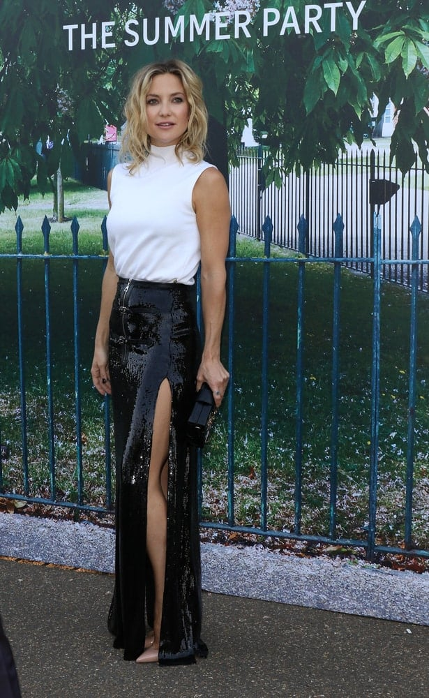 Kate Hudson was quite fashionable in her white blouse and black sequined skirt that she paired with a shoulder-length tousled wavy hairstyle when she attended the Serpentine Gallery Summer Party at Kensington Gardens on Jul 2, 2015, in London.