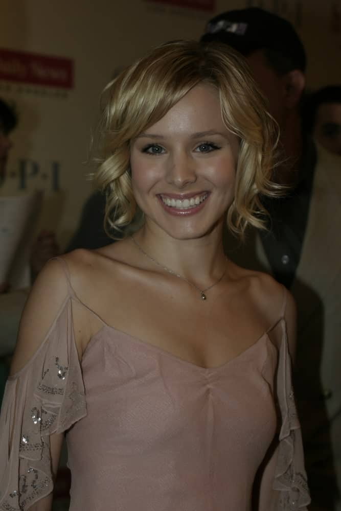 "Kristen Bell looked charming in a cold shoulder dress that goes perfectly with her short blonde waves with side-swept bangs. This was taken at the Los Angeles Opening Night of ""Hairspray"" held at the Pantages Theatre on July 21, 2004."