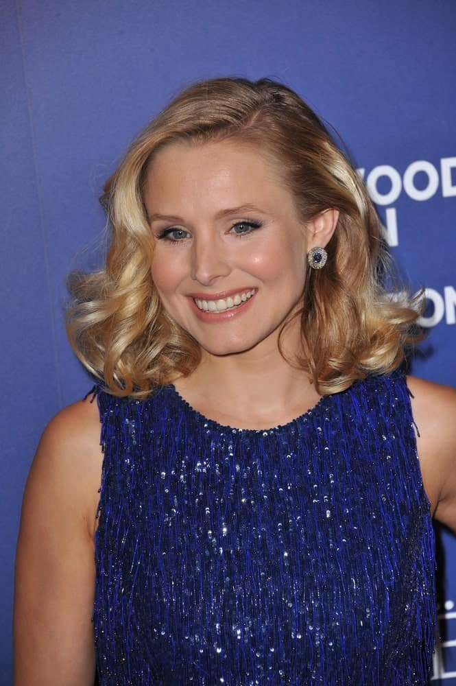 Kristen Bell in a blue sparkling dress that contrasts her blonde voluminous waves during the Hollywood Foreign Press Association's annual Grants Banquet on August 14, 2014.