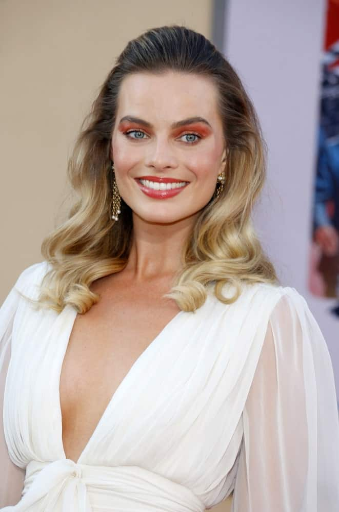 Margot Robbie paired her sheer white dress with a wavy half updo during the Los Angeles premiere of 'Once Upon a Time In Hollywood' held at the TCL Chinese Theatre IMAX on July 22, 2019.