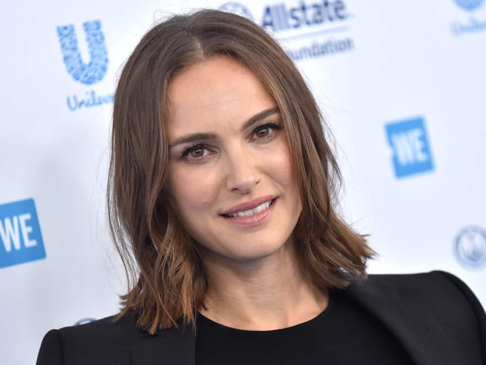 Natalie Portman was at the WE Day California 2019 on April 25, 2019, in Inglewood, CA. She came wearing a black smart casual outfit to match her simple make-up and loose layered bob hairstyle with a slight tousle and long side bangs.