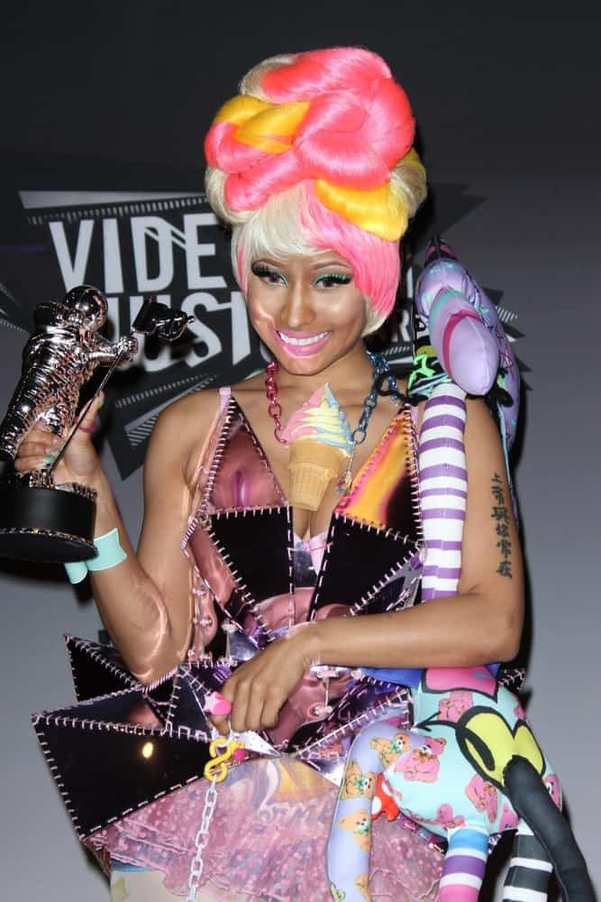 Nicki Minaj flaunted her hard-earned trophy at the 2011 MTV Video Music Awards Press Room in Nokia Theatre LA Live, Los Angeles, CA on August 28, 2011. She wore an artistic and colorful outfit that she paired with an equally colorful beehive bun hairstyle with bangs.