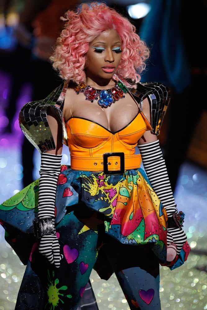 Nicki Minaj performed on the runway during the 2011 Victoria's Secret Fashion Show at the Lexington Avenue Armory on November 9, 2011, in New York City. She was seen with a colorful and artistic outfit with her pink-dyed curly shoulder-length hairstyle.