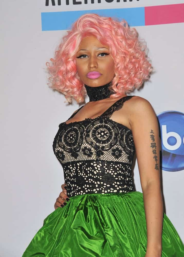 Nicki Minaj was at the 2011 American Music Awards at the Nokia Theatre L.A. Live in downtown Los Angeles on November 20, 2011, Los Angeles, CA. She wore a black and green lovely dress with her shoulder-length curly tousled pink hairstyle.
