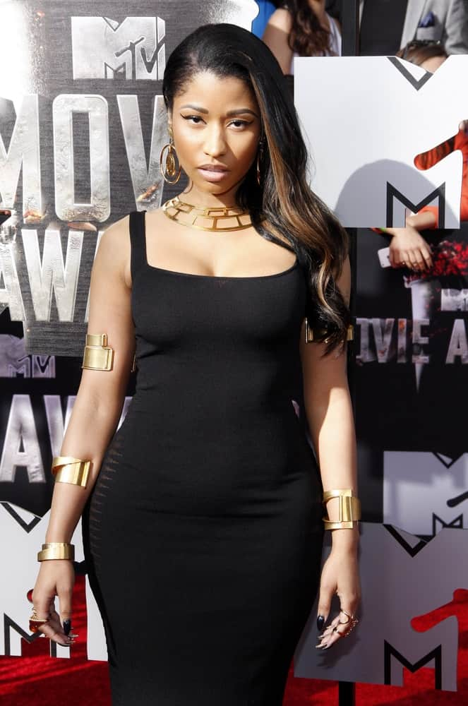 Nicki Minaj wore a form-hugging black dress that she paired well with a side-swept wavy black hairstyle that has brown highlights at the 2014 MTV Movie Awards held at the Nokia Theatre L.A. Live in Los Angeles, USA on April 13, 2014.