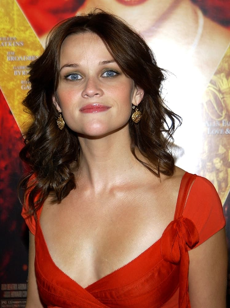 Reese Witherspoon dyed her hair into a dark brown tone and styled it into a tousled, curly and layered hairstyle loose on her shoulders at the premiere of VANITY FAIR at the Clearview Theater on August 16, 2004, in New York.