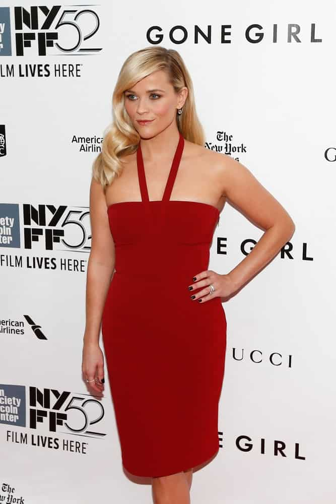 "Actress Reese Witherspoon wore a lovely red dress to pair with her side-swept curly blond hairstyle with long side-swept bangs at the world premiere of ""Gone Girl"" on the 52nd New York Film Festival at Alice Tully Hall on September 26, 2014, in New York City."