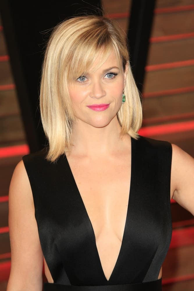 Reese Witherspoon wore a stunning black dress that she complemented with a simple layered blond bob hairstyle with bangs at the 2014 Vanity Fair Oscar Party at the Sunset Boulevard on March 2, 2014, in West Hollywood, CA.