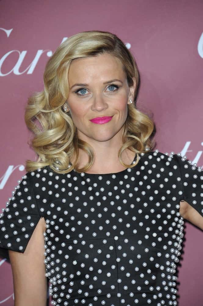 On January 6, 2015, Reese Witherspoon was at the 2015 Palm Springs Film Festival Awards Gala at the Palm Springs Convention Centre. She paired her black pearly dress with cute pink lips and side-swept curly blond hairstyle with layers and highlights.