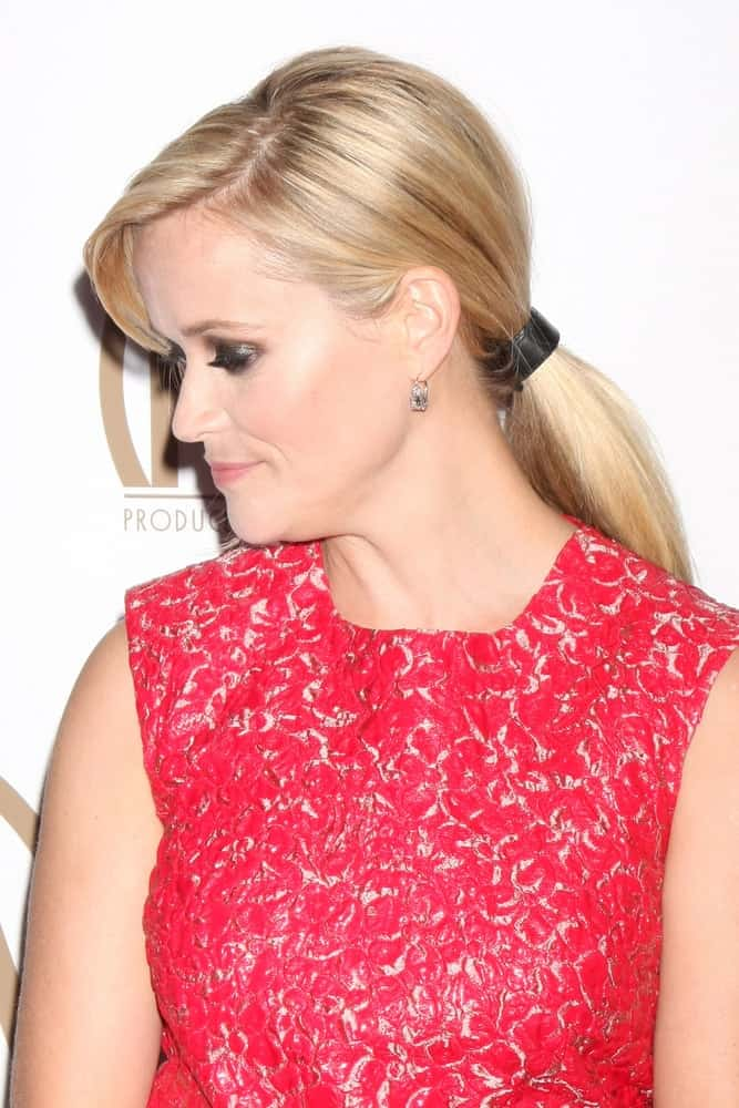 On January 25, 2015, Reese Witherspoon attended the 26th Annual Producers Guild Awards at the Hyatt Regency Century Plaza Hotel. She wore a charming red outfit that paired quite well with her blond low ponytail with side-swept bangs.