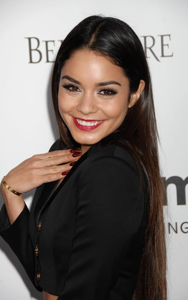 Vanessa Hudgens wore a black two-piece black suit with her long and layered straight hairstyle loose on her back at the 4th Annual amfAR Inspiration Gala on December 12, 2013, in Los Angeles, CA.