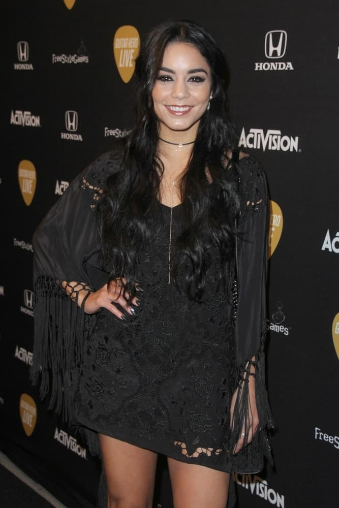 Vanessa Hudgens' short frilly black dress went quite well with her long and loose wavy hairstyle that has a slightly tousled finish at the Guitar Hero Live Launch Party at the YouTube Space LA on October 19, 2015, in Los Angeles, CA.