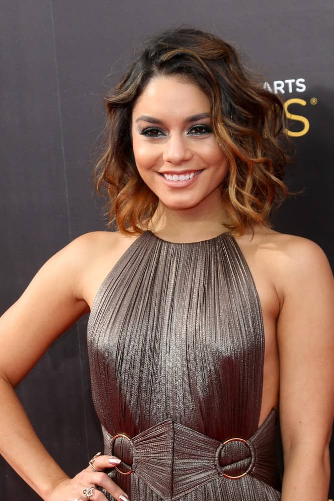 Vanessa Hudgens was at the 2016 Primetime Creative Emmy Awards – Day 2 – Arrivals at the Microsoft Theater on September 11, 2016, in Los Angeles, CA. She wore an elegant silver dress that pairs quite well with her short tousled curly hair with highlights.