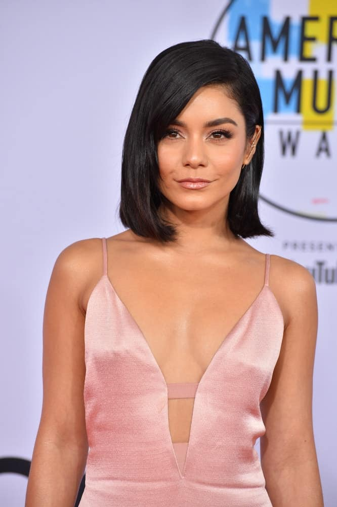 On October 09, 2018, Vanessa Hudgens wore a charming pink dress that she paired with her straight, layered and loose raven bob hairstyle that has flippy tips at the 2018 American Music Awards at the Microsoft Theatre LA Live in Los Angeles, CA.