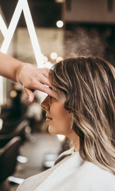 Hair stylist applying hair spray to woman