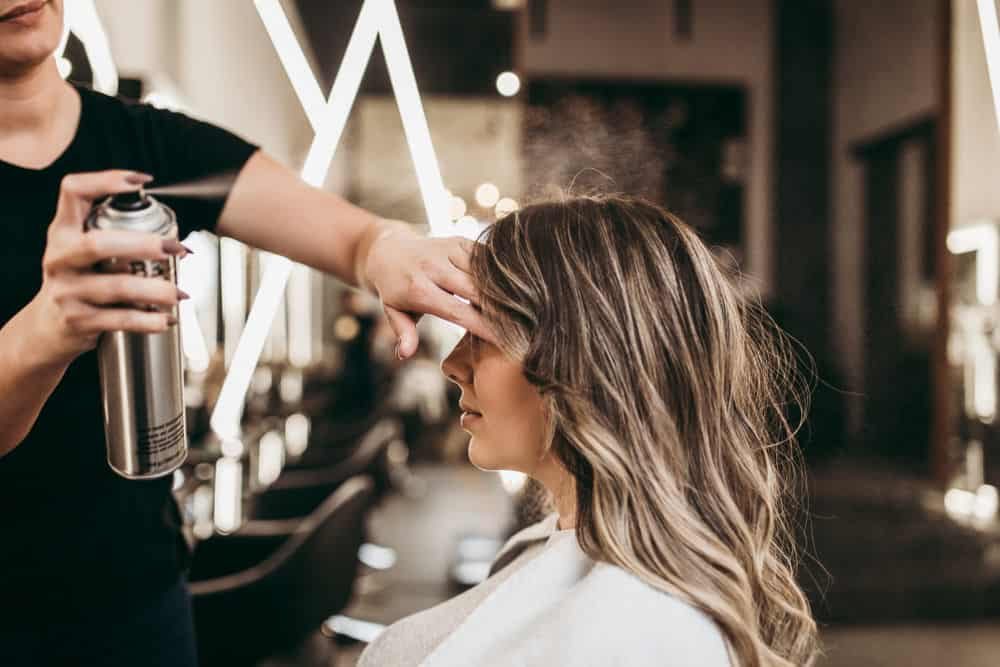 Hair stylist applying hair spray to woman