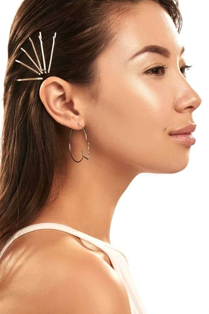 Side profile of a beautiful woman wearing bobby pins.