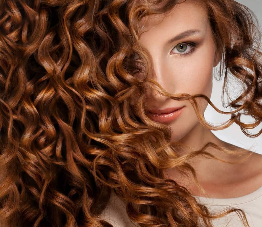 Woman with thick curly auburn hair.