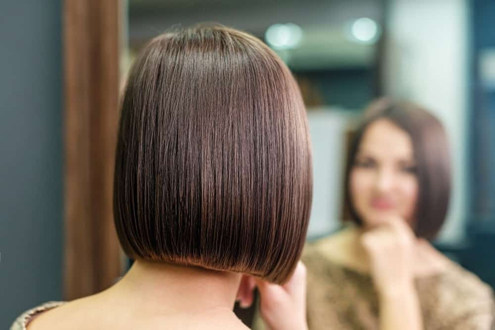 A woman with a plain bob hairstyle looking at herself in the mirror.