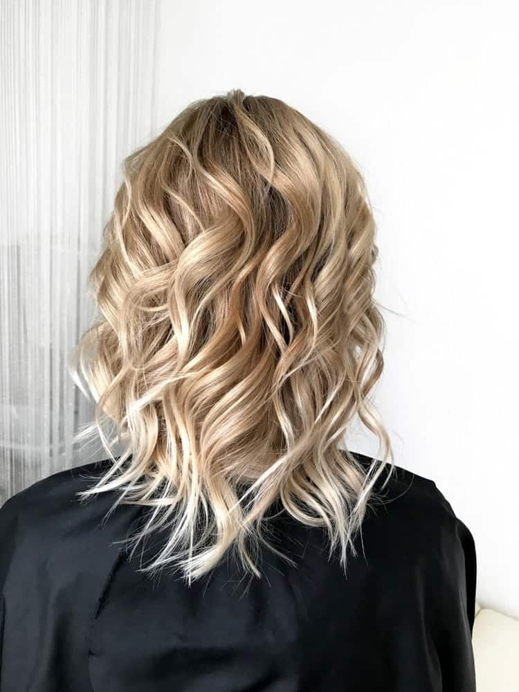 A woman with short blond hair that has lots of waves.