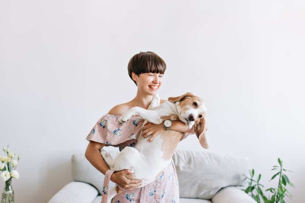 A woman with a bowl cut hairstyle carrying a dog.