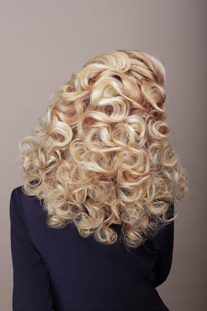 A woman with blond loose curls as seen from behind.