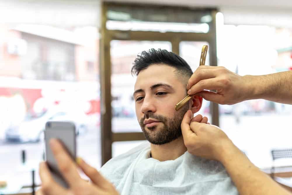 A man checks his phone while getting a haircut.