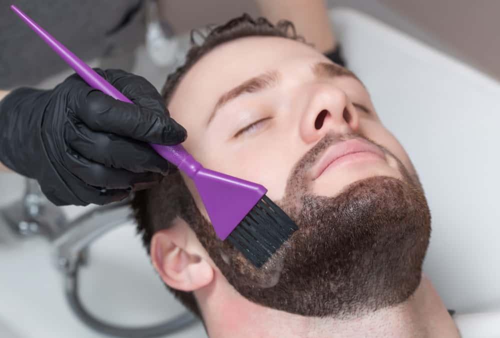 A close look at a man having his beard dyed.