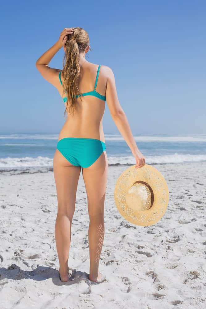 Woman in green swimsuit and beach wave pony holding her hat on the beach.