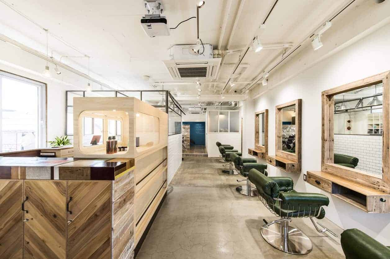 Hair salon interior with white walls, concrete flooring, chevron reception, and green leather chairs paired with wooden framed mirrors.