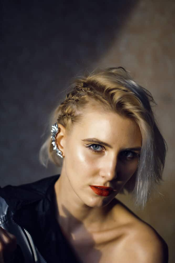 A woman with side-swept short blonde hair and braided three spikelets.
