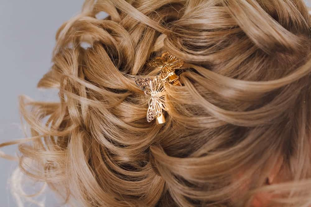 Woman's brown curly hair pinned with butterfly clips.