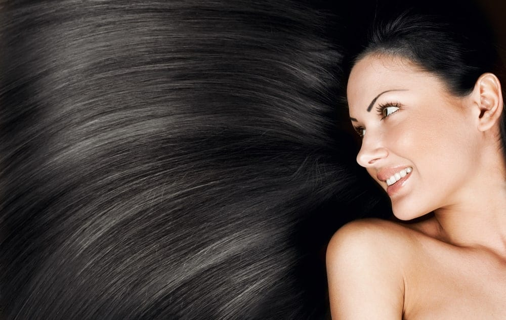 A woman with a background of dark silky hair.