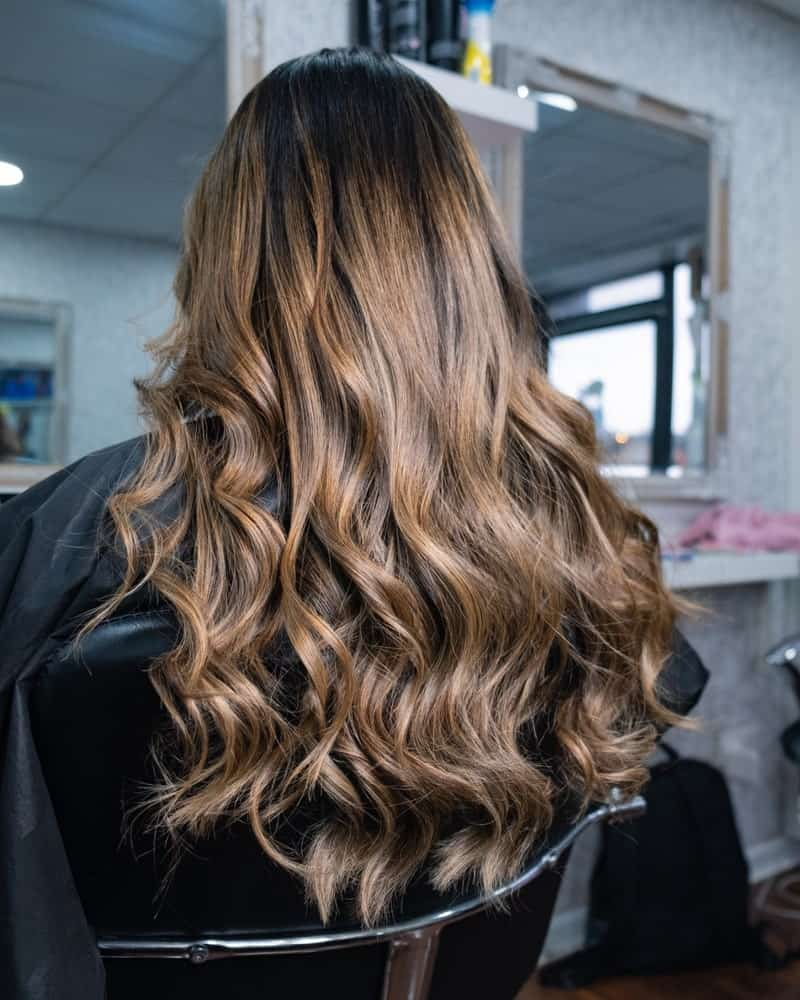 A woman with a long and wavy balayage hairstyle.