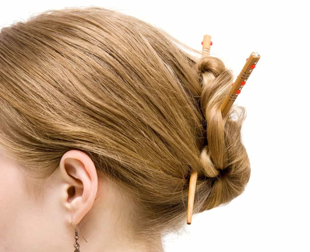 Side profile of a woman's head with her hair tied with chopsticks.