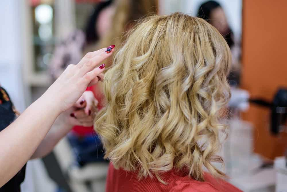 Female hairdresser styling the woman's blonde hair.