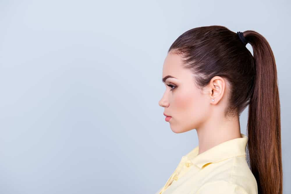 Side profile of a woman in yellow polo shirt with a high ponytail.