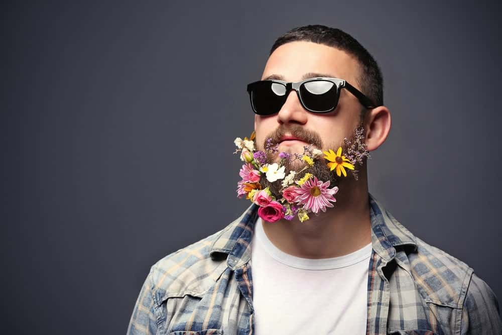 Man in sunglasses with beard of flowers.