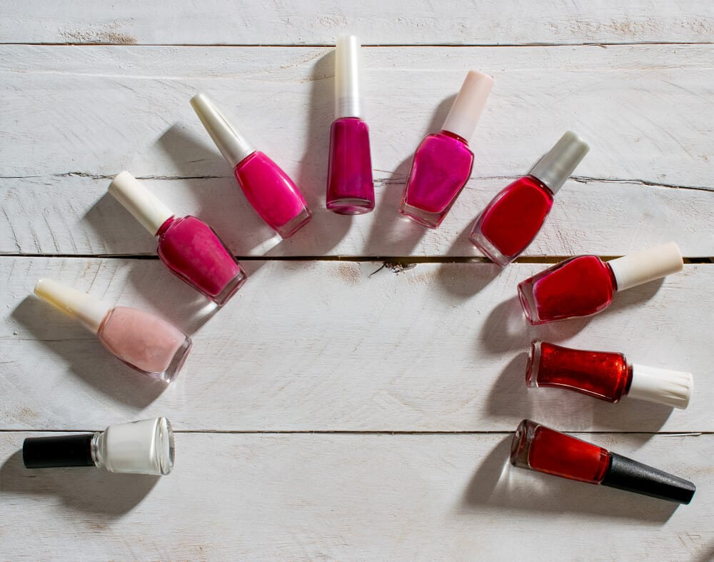 Nail polish bottles on a semi-circle against a whitewashed pallet background.