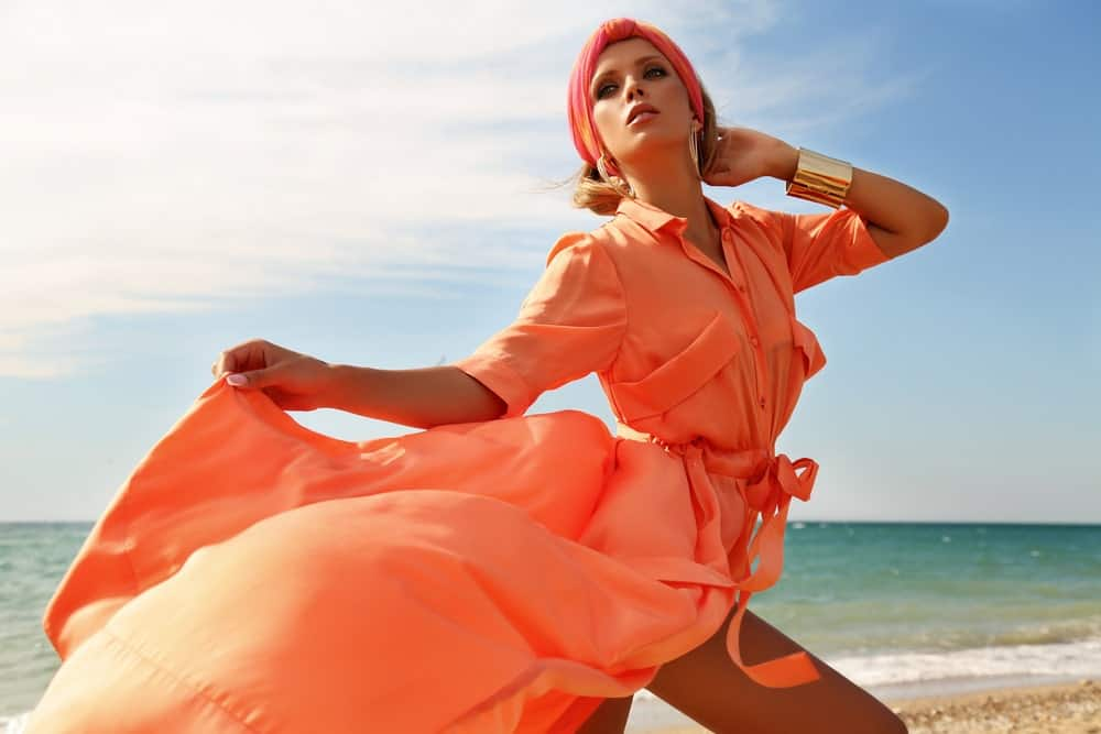 Woman in an orange dress and a matching hair scarf on the beach.