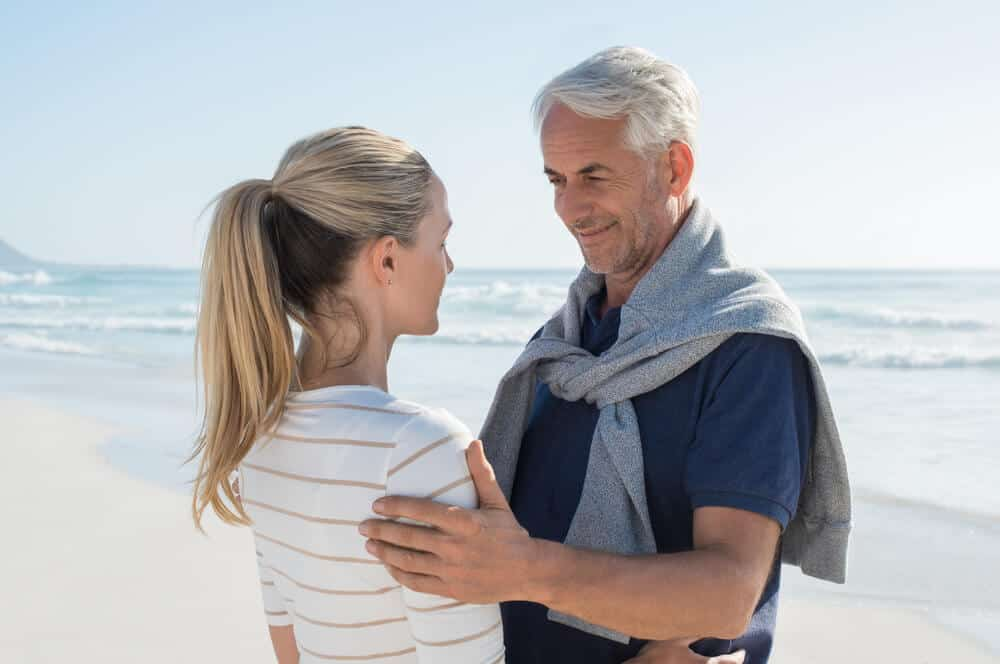 An elderly couple looking at each other at a beachside.