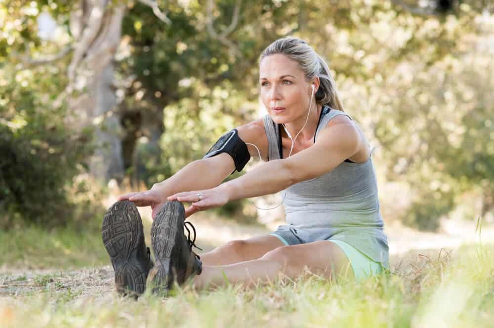 An elder woman doing an exercise outdoors.