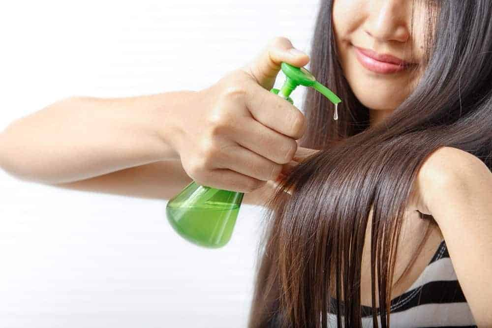 A woman pumping some hair oil into her long, straight hair.