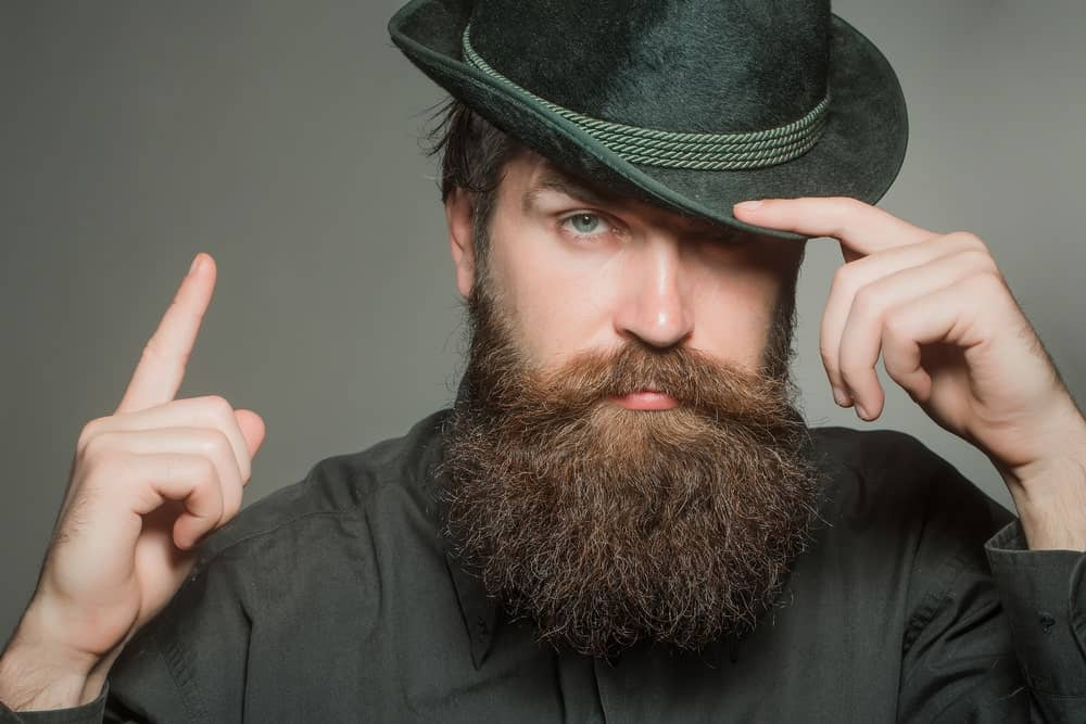 Man with long beard and mustache in a stylish black retro hat.