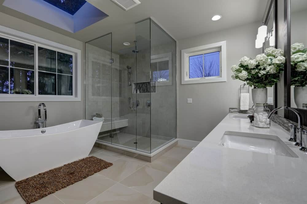 Gray bathroom with a walk-in shower, a freestanding tub, and a dual sink vanity.
