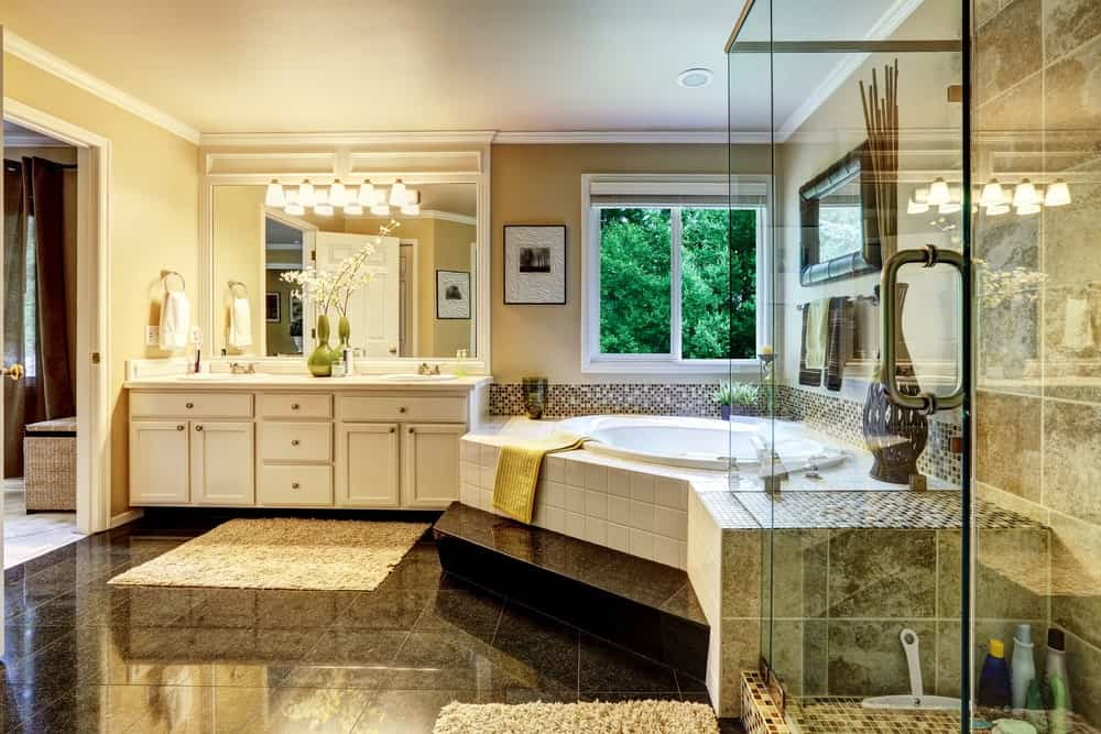 Luxury bathroom interior with walk-in shower, corner tub, and a white vanity.