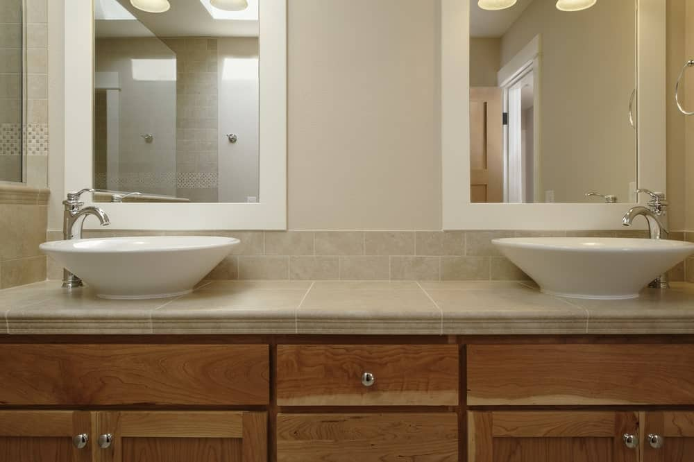 Wooden vanity with his and her vessel sinks.