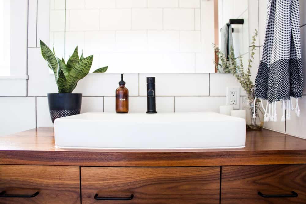 Wooden vanity topped with a vessel porcelain sink and a small potted plant.