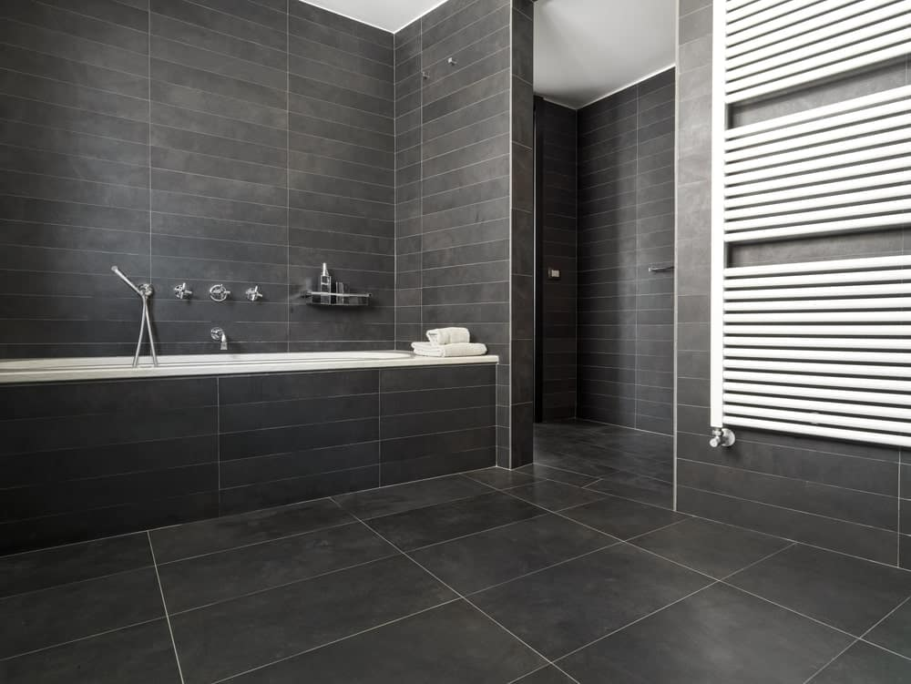 Modern bathroom with a drop-in bathtub clad in gray tiles that match the walls and flooring.